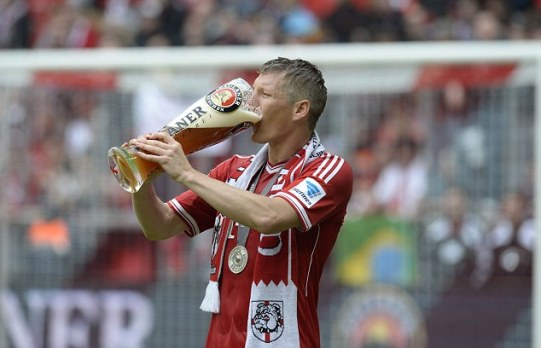 Bayern Munich's midfielder Bastian Schweinsteiger drinks a beer as he celebrates after winning 3:0 the German first division Bundesliga football match Bayern Munich vs FC Augsburg in Munich, southern Germany, on May 11, 2013. Munich were confirmed German league champions back on April 6, when they won the Bundesliga with a record six games left to play. AFP PHOTO / CHRISTOF STACHE RESTRICTIONS / EMBARGO - DFL RULES TO LIMIT THE ONLINE USAGE DURING MATCH TIME TO 15 PICTURES PER MATCH. IMAGE SEQUENCES TO SIMULATE VIDEO IS NOT ALLOWED AT ANY TIME. FOR FURTHER QUERIES PLEASE CONTACT THE DFL DIRECTLY AT + 49 69 650050.CHRISTOF STACHE/AFP/Getty Images