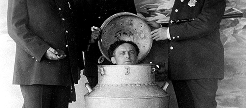 Harry Houdini performs the great milk can escape c.1908 (sepia photo)